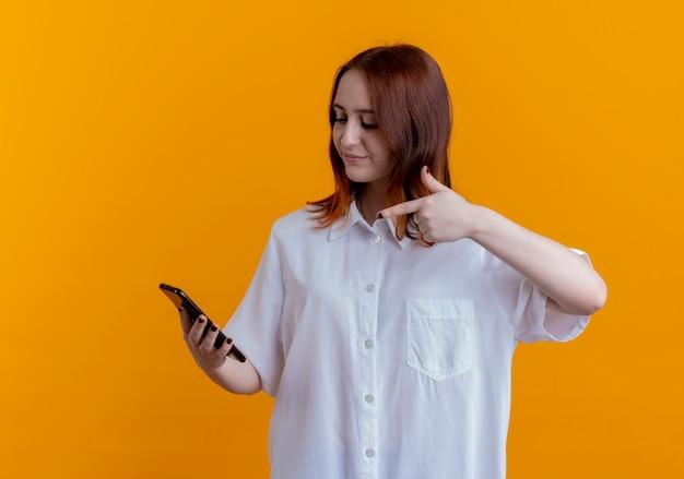 黄色で隔離の電話を保持し、ポイントする若い赤毛の女性を喜ばせる