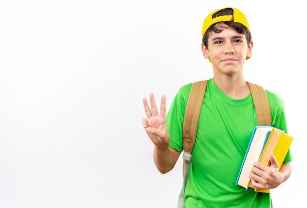コピースペースで白い壁に隔離された3つを示す本を保持しているキャップ付きのバックパックを身に着けている若い男子生徒を喜ばせる