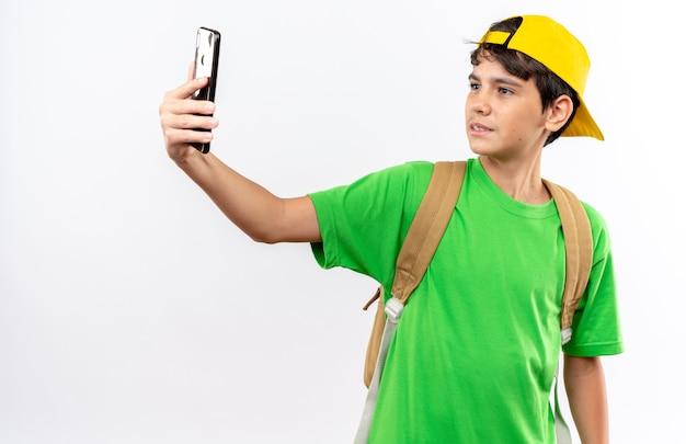 キャップ付きのバックパックを身に着けている満足している若い男子生徒は白い壁に隔離されたselfieを取る