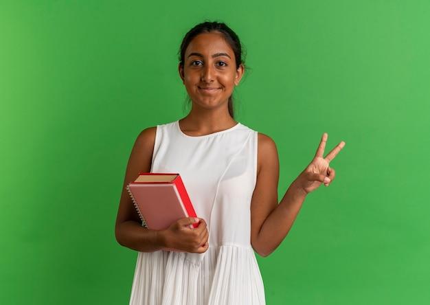 ノートブックで本を保持し、緑に平和のジェスチャーを示す若い女子高生を喜ば
