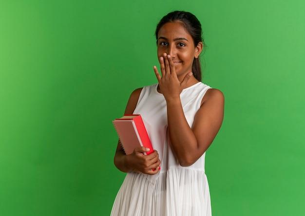 Lieta giovane studentessa tenendo il libro con notebooke e la bocca coperta con la mano sul verde