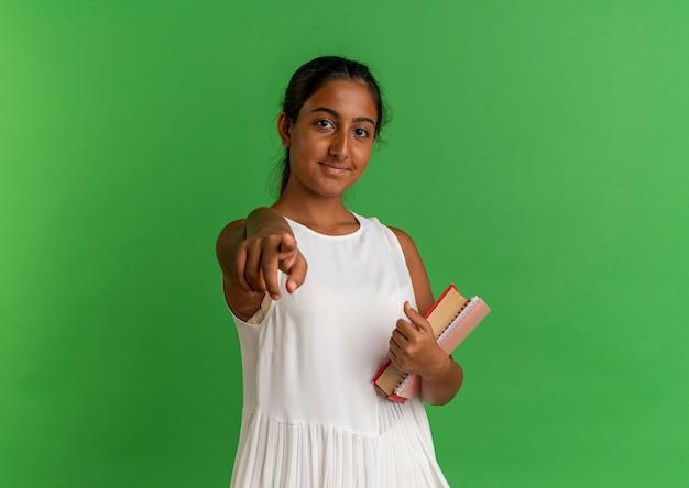 Довольная молодая школьница держит тетрадь с книгой и показывает жест на зеленом