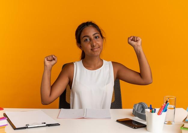 강한 제스처를 하 고 학교 도구로 책상에 앉아 기쁘게 젊은여 학생