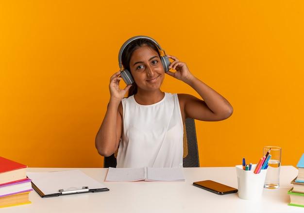 Довольная молодая школьница сидит за столом со школьными инструментами, слушает музыку в наушниках, изолированных на оранжевой стене