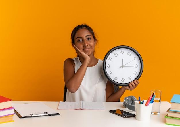 Felice giovane studentessa seduto alla scrivania con strumenti di scuola tenendo l'orologio da parete e mettendo la mano sulla guancia sull'arancia