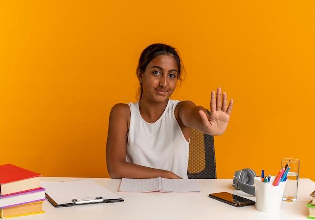 Pleased young schoolgirl sitting at desk with school tools showing stop gesture on orange