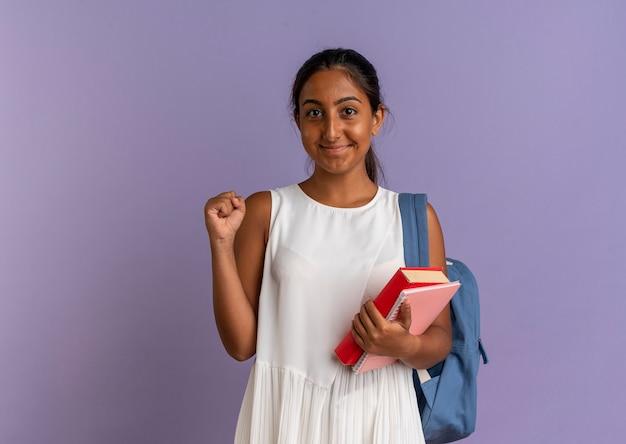 本とノートを保持しているバックバッグを身に着けている若い女子高生が紫色ではいジェスチャーを示していることを喜んで