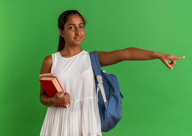 ノートブックと緑で隔離された側のポイントで本を保持しているバックバッグを身に着けている若い女子高生を喜ばせる