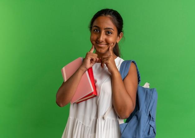 ノートブックと本を保持し、緑で隔離の頬に指を置くバックバッグを身に着けている若い女子高生を喜ばせる