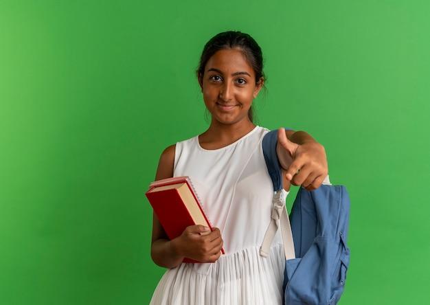 노트북과 책을 들고 녹색에 제스처를 보여주는 다시 가방을 입고 기쁘게 어린 여학생