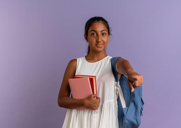 노트북과 책을 들고 보라색에 제스처를 보여주는 다시 가방을 입고 기쁘게 어린 여학생