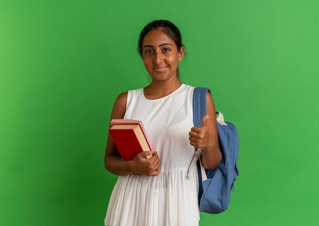 緑の上に彼女の親指をノートブックで本を保持しているバックバッグを身に着けている若い女子高生を喜ばせる