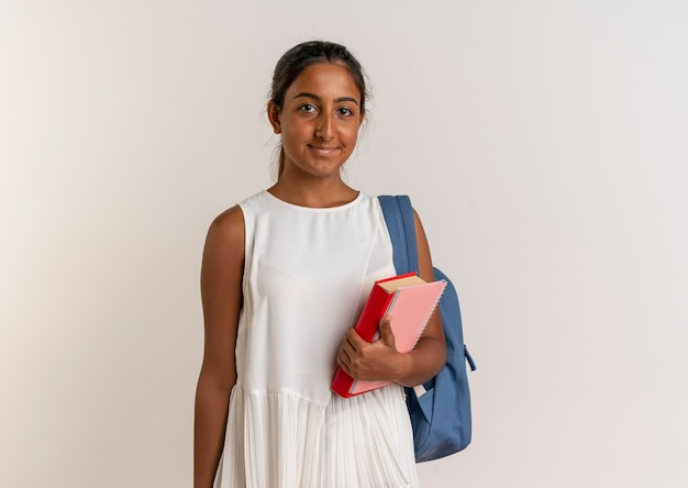 白のノートと本を保持しているバックバッグを身に着けている若い女子高生を喜ばせる