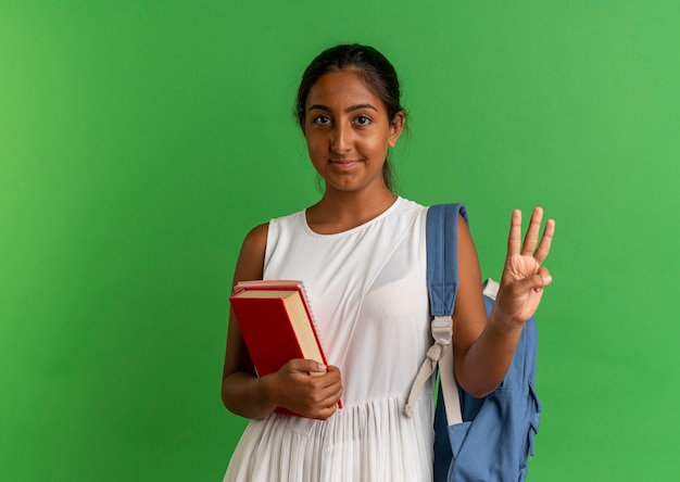 Lieta giovane studentessa che indossa la borsa indietro tenendo il libro con il taccuino e mostrando con la mano tre sul verde
