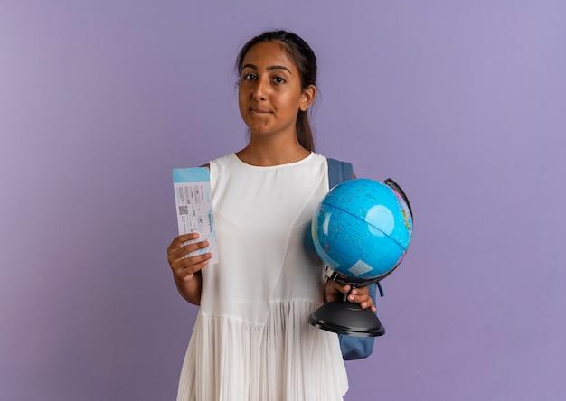 Piacere giovane studentessa che indossa la borsa posteriore tenendo il globo e il biglietto sulla porpora