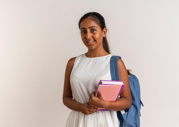 白のノートを保持しているバックバッグを身に着けている若い女子高生を喜ばせる