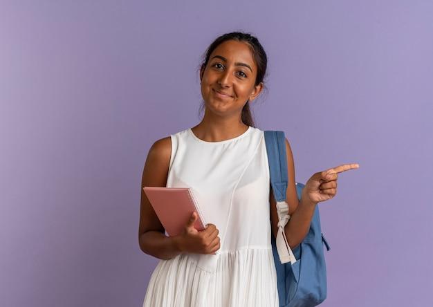 Piacere giovane studentessa che indossa il taccuino della holding della borsa posteriore e indica il lato sul viola