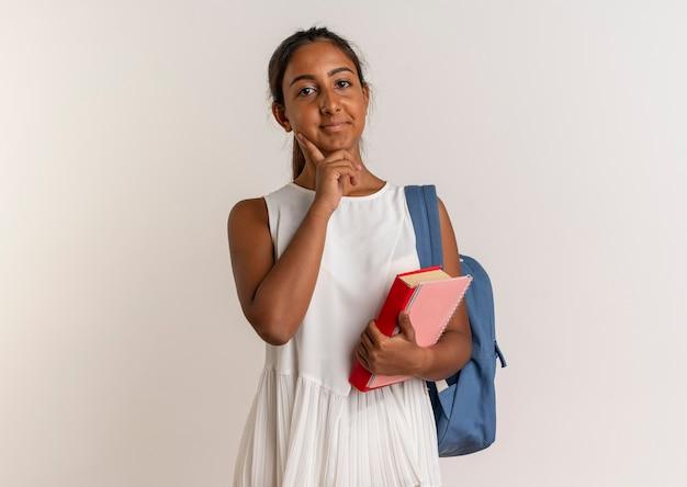 Довольная молодая школьница в задней сумке держит блокнот с книгой и кладет палец на щеку на белом