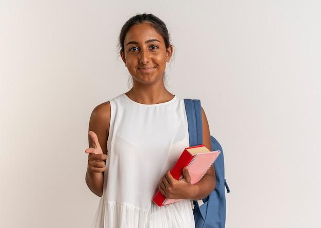 책과 노트북을 들고 화이트 제스처를 보여주는 다시 가방을 입고 기쁘게 젊은 여학생