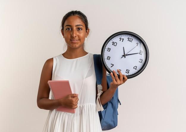 Compiaciuto giovane studentessa che indossa la borsa indietro azienda notebook con orologio da parete