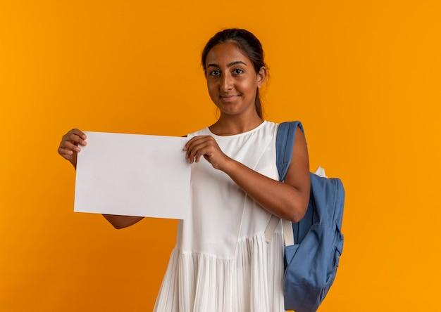 Soddisfatto giovane studentessa che indossa la borsa posteriore tenendo la carta sull'arancio