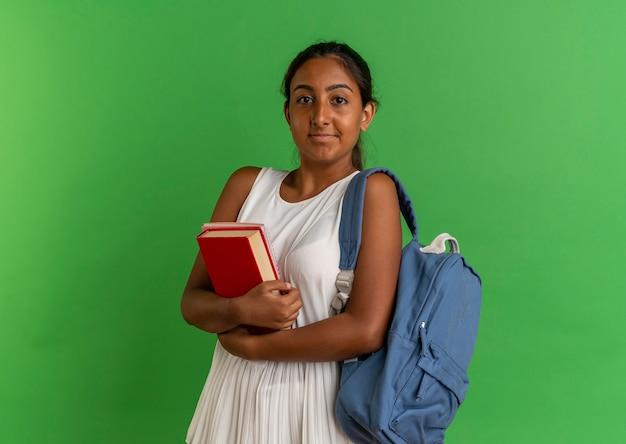 緑に分離されたノートブックとバックバッグ抱きしめ本を身に着けている若い女子高生を喜ばせる