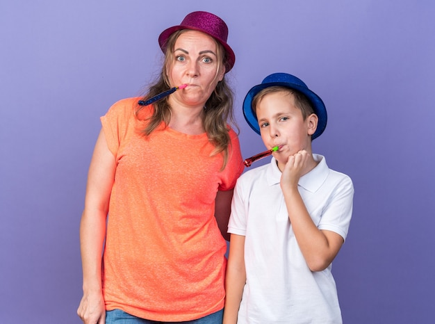 Pleased young slavic boy with blue party hat blowing party whistle together with his mother wearing violet party hat isolated on purple wall with copy space