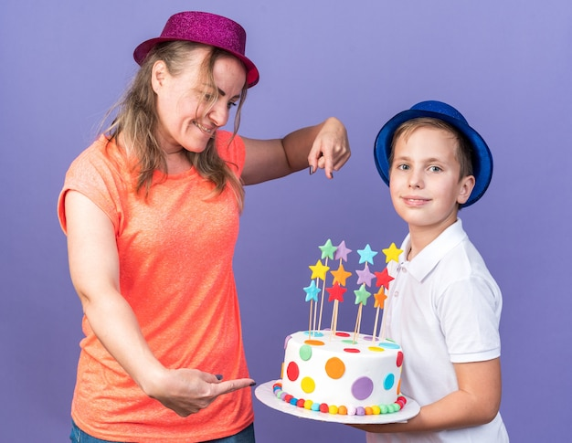 Pleased young slavic boy with blue party hat holding birthday cake standing with his mother wearing violet party hat and pointing at cake isolated on purple wall with copy space