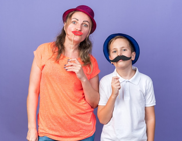 Felice giovane ragazzo slavo con cappello da festa blu che tiene baffi finti su un bastone in piedi con sua madre che indossa un cappello da festa viola e tiene labbra finte su un bastone sul muro viola