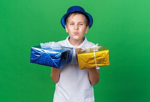 コピースペースで緑の壁に分離された両手にギフトボックスを保持している青いパーティーハットと喜んで若いスラブ少年