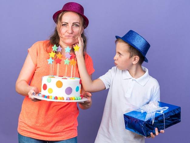 Pleased young slavic boy with blue party hat holding gift box and pulling cheek of his mother wearing violet party hat and holding birthday cake isolated on purple wall with copy space