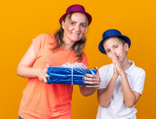 Pleased young slavic boy with blue party hat holding hands together and standing with his mother wearing purple party hat and holding gift box isolated on orange wall with copy space