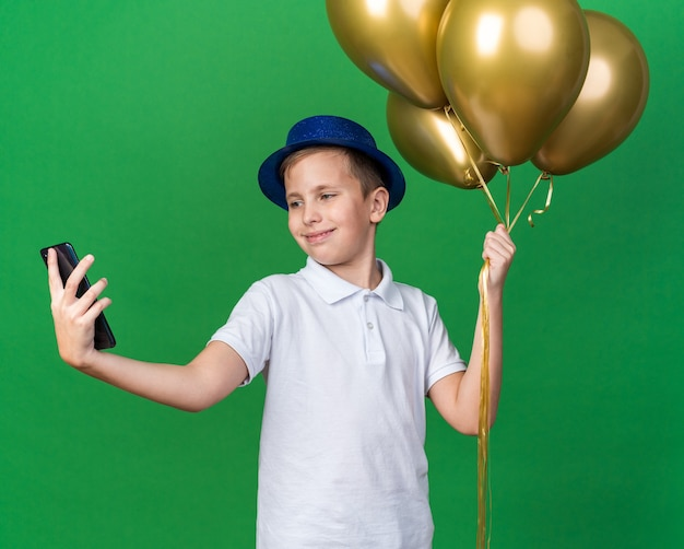 헬륨 풍선을 들고 복사 공간이 녹색 벽에 고립 된 전화에 셀카를 복용 파란색 파티 모자와 함께 기쁘게 젊은 슬라브 소년