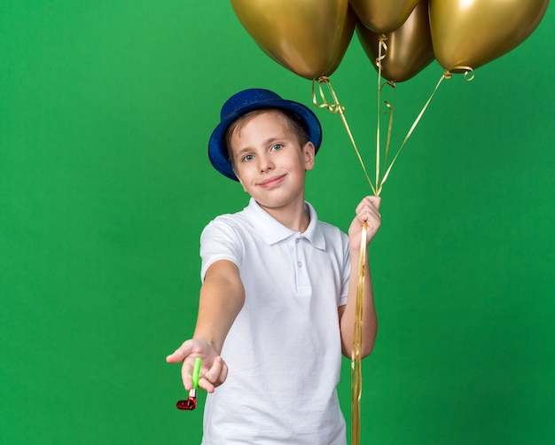 Pleased young slavic boy with blue party hat holding helium balloons and party whistle isolated on green wall with copy space