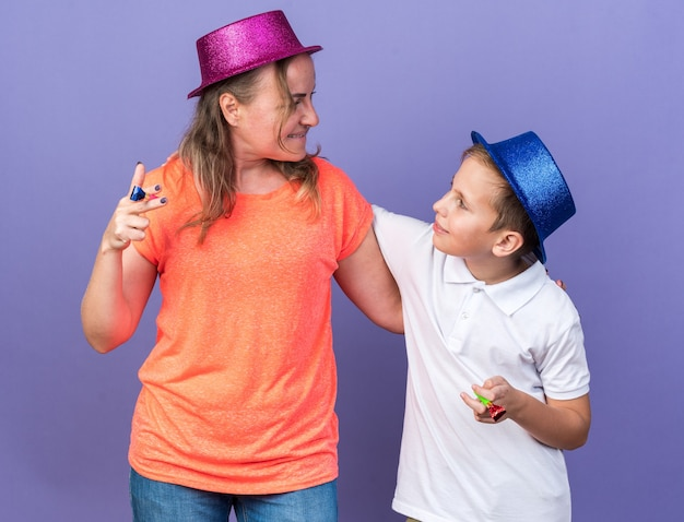 Pleased young slavic boy with blue party hat holding party whistles together with his mother wearing violet party hat isolated on purple wall with copy space