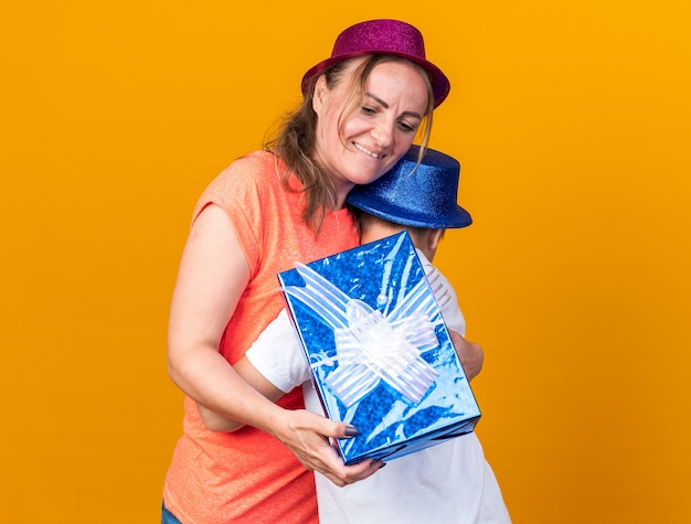 Pleased young slavic boy with blue party hat hugging his mother wearing violet party hat and holding gift box isolated on orange wall with copy space