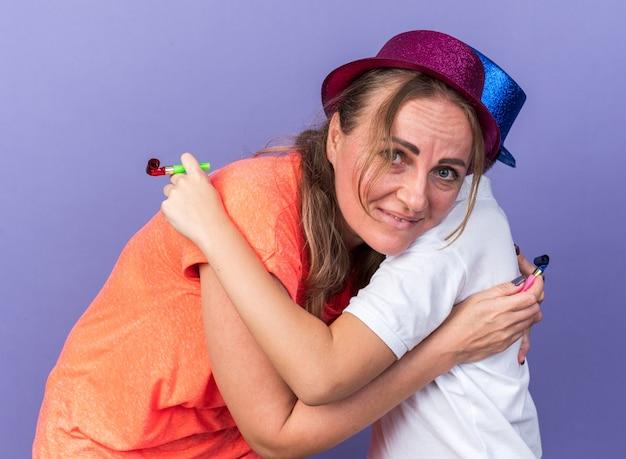Felice giovane ragazzo slavo con cappello blu del partito che abbraccia sua madre che indossa il cappello viola del partito e che tiene il fischio del partito isolato sulla parete viola con lo spazio della copia