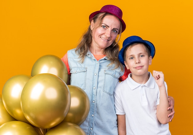 Pleased young slavic boy with blue party hat keeping fist and standing with his mother wearing purple party hat holding helium balloons isolated on orange wall with copy space