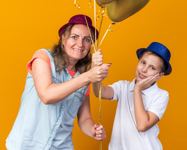 Pleased young slavic boy with blue party hat putting hand on face and holding helium balloons with his mother wearing purple party hat isolated on orange wall with copy space