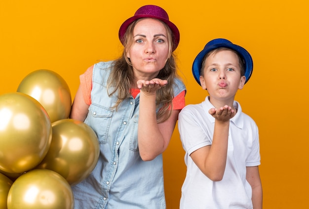 Pleased young slavic boy with blue party hat sending kiss with hand and standing with his mother wearing purple party hat holding helium balloons isolated on orange wall with copy space