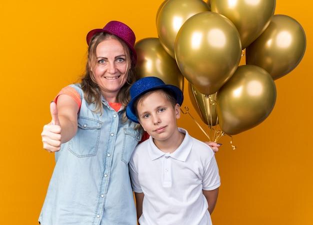 Felice giovane ragazzo slavo con cappello da festa blu in piedi con sua madre che indossa cappello da festa viola con palloncini di elio e pollice in alto isolato sul muro arancione con spazio di copia