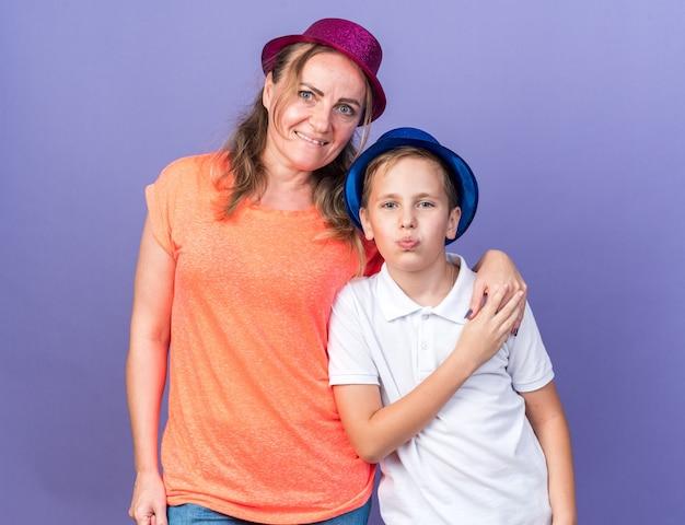 Lieto giovane ragazzo slavo con cappello da festa blu in piedi con sua madre che indossa cappello da festa viola isolato sul muro viola con spazio di copia