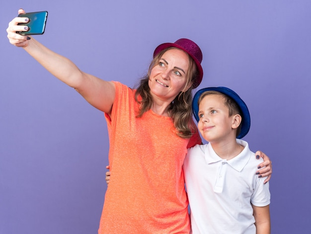 Pleased young slavic boy with blue party hat taking selfie with his mother wearing violet party hat isolated on purple wall with copy space