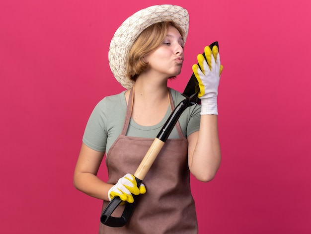 ピンクのスペードにキスをするふりをして、園芸用の帽子と手袋をかぶった若いスラブの女性の庭師を喜ばせます