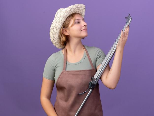 보라색에 잎 갈퀴를 들고 원예 모자를 쓰고 기쁘게 젊은 슬라브 여성 정원사