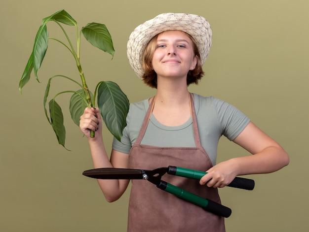 コピースペースのあるオリーブグリーンの壁に隔離されたガーデニングはさみと植物を保持しているガーデニング帽子をかぶっている若いスラブ女性の庭師を喜ばせる