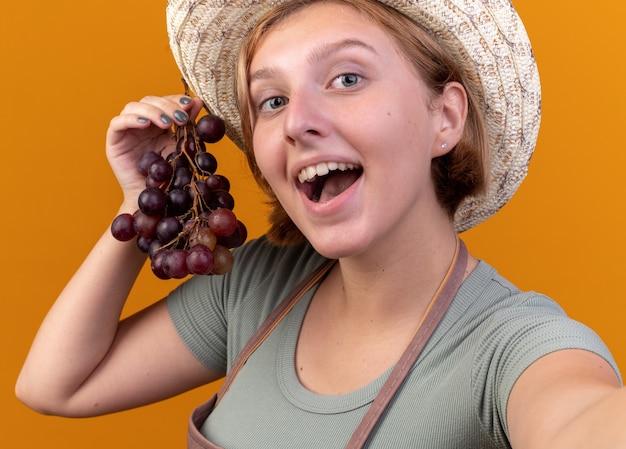 Lieta giovane femmina slava giardiniere che indossa cappello da giardinaggio tenendo l'uva guardando la fotocamera prendendo selfie