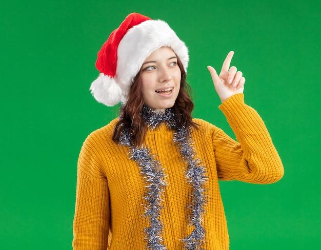 Довольная молодая славянская девушка в новогодней шапке и с гирляндой на шее смотрит и указывает на сторону, изолированную на зеленой стене с копией пространства