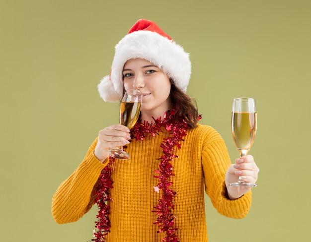 Lieta giovane ragazza slava con cappello da babbo natale e con ghirlanda intorno al collo beve e tiene bicchieri di champagne isolati su parete verde oliva con spazio di copia