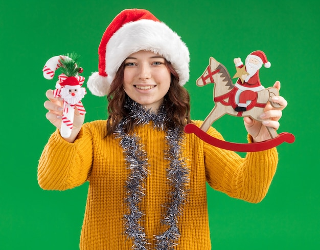 Pleased young slavic girl with santa hat and with garland around neck holding candy cane and santa on rocking horse decoration isolated on green background with copy space